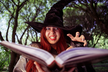 Photo of sinister witch with book of spells