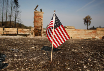 An American flag stands in front of a home destroyed after a wildfire tore through Santa Rosa, California