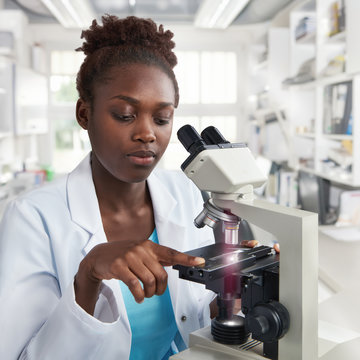 African-american female scientist, student or tech works with a microscope