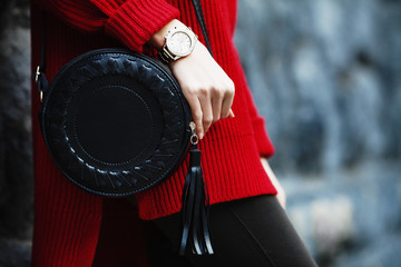 Fashionable woman posing in street, near wall, holding black round bag, wearing wrist watch, stylish red oversized sweater. Female fashion concept. Copy, empty space for text.