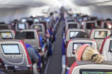 Passengers traveling by a new jet plane, shot from the inside of an airplane