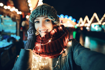 Outdoor close up portrait of young beautiful happy smiling girl making selfie photo in night street. Festive Christmas fair on background. Model looking at camera, wearing knitted beanie hat, scarf.