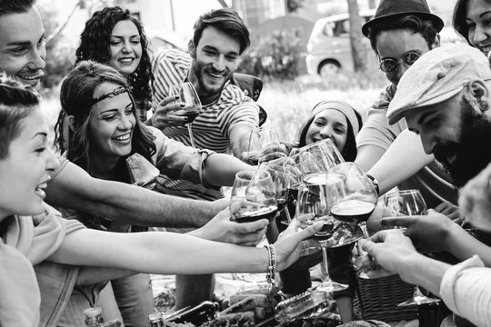 Group of people cheering with red glasses of wine - Happy young friends enjoying picnic in a park with food e drink - Black and white edit - Youth concept - Focus on woman with band on the left