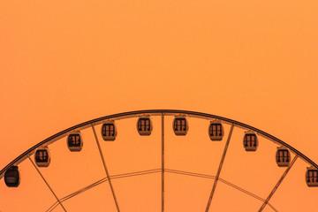 Ferris wheel on golden background vintage color with sunset background.Colorful vintage retro ferris wheel on orange sky, Thailand