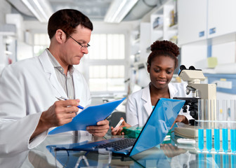 Scientists, Caucasian male and African female, work in laboratory