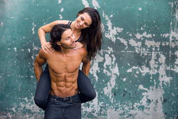 Fun high spirited loving healthy muscular fit couple are playful with a piggyback ride