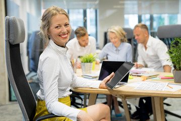 Happy woman in office working in group