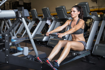 Fit toned thin woman exercising on a fitness machine for weight loss and stamina building at the gym