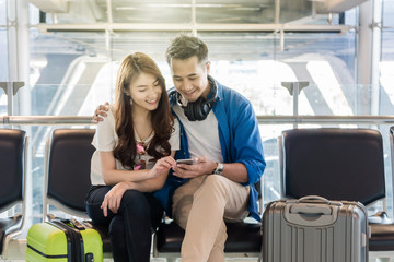 Happiness Asian couple traveler with suitcases using the smart phone in modern an airport, travel and transportation with technology concept.