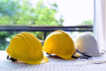 White and two yellow hard safety helmet hat for safety project of workman as engineer or worker, on architect working table .