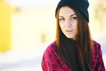 Closeup portrait of cute young woman with long hair and blue eyes. Girl in a plaid jacket and black hat looking at the camera. Natural beauty. Street fashion.