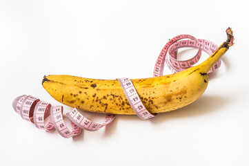 Yellow banana with measuring tape - diet concept
