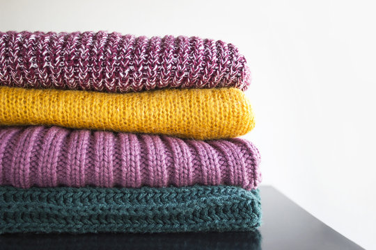 Stack of various sweaters for winter and autumn on white background