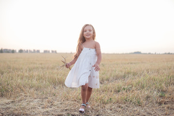 Little beautiful smiling girl on a gold wheat field walking at sunset. Happy five years old girl smiling and laughing in summer day at nature. Happyness freedom and carefree childhood concept