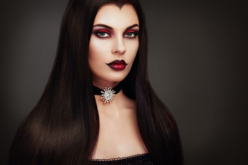Halloween Vampire Woman portrait. Beautiful Glamour Fashion Sexy Vampire Lady with long dark Hair, beauty make up and Costume
