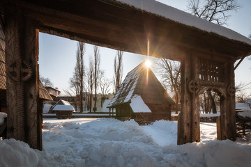 Sun star warming up a traditional Romanian homestead covered in heavy snow