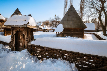 Traditional handcrafted gate and a rural Romanian homestead covered in snow