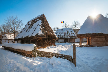 Sun warming up a traditional Romanian homestead covered in heavy snow