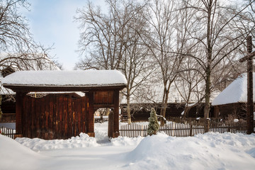 Traditional wooden gate and a homestead in a winter setting at the Village Museum in Bucharest, Romania.
