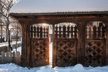 A traditional handcrafted wooden Gate at the Village Museum in Bucharest, Romania in winter.