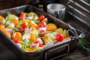 Preparation for grilled homemade potato with tomatoes, garlic and rosemary
