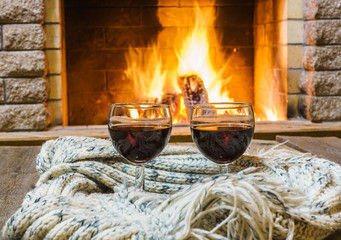 Two  glasses  of  red  vine  and  woolen things near  cozy fireplace, in country house, winter vacation, horizontal.