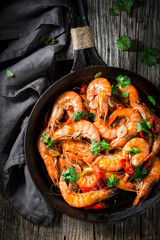 Tasty shrimps on pan with garlic, coriander and peppers