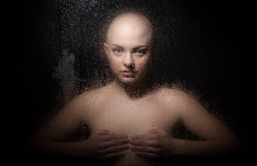 Portrait of a bald girl behind a wet glass on a black background.