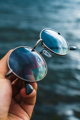 Crop hand holding sunglasses above water