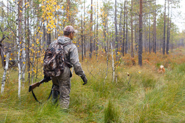 Foto op Aluminium Jacht hunter in camouflage with shotgun walking in the forest