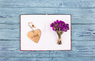 An open diary, a wooden heart and flowers. Romantic concept. Wood valentine