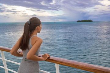 Wall Mural - Luxury cruise vacation woman looking at French Polynesia motu island from boat deck at sunset. Elegant tourist relaxing at view of ocean scenery at dusk, relaxing outdoor. Sailing lifestyle holidays.
