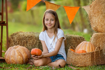 Cute young girl sitting among hay bales and pumpkins in the garden