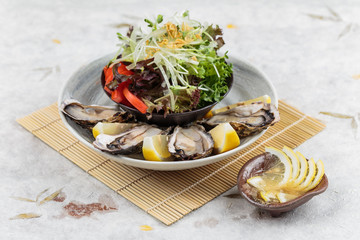 Fresh oysters and Japanese salad served with Sliced and lemon sauce on white stone bowl on makisu (meal mat).