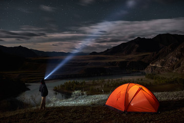Male tourist with flashlight near his camp tent at night.