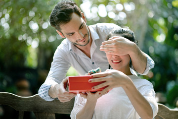 Young man is covering his girlfriend eyes and giving her a present
