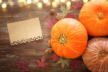 Pumpkins and autumn leaves on wooden background. thanksgiving and halloween concept