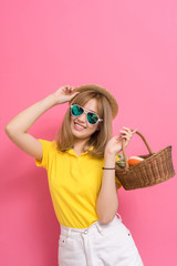 Fashion portrait of girl shopping concet. young beautiful asian with relax dress yellow shirt and white jeans pants, hat, sunglasses, basket vegetables in summer lifestyle on pink background.