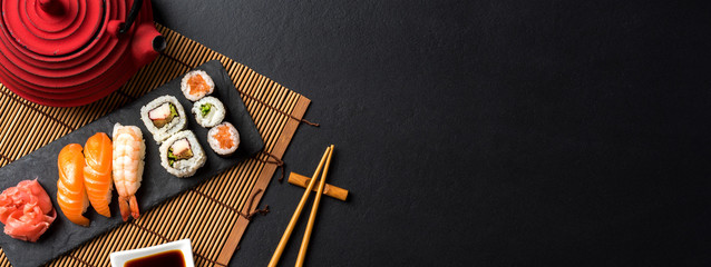 Fotobehang Sushi bar Set of sushi with wasabi, soy sauce and teapot on black stone background