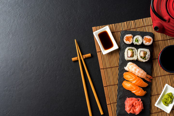 Aluminium Prints Sushi bar Set of sushi with wasabi, soy sauce and teapot on black stone background