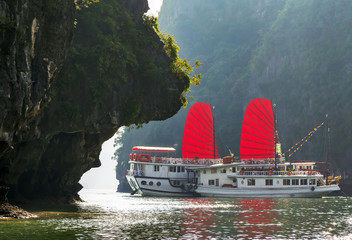 Halong bay sunrise and Vietnam traditional boat.