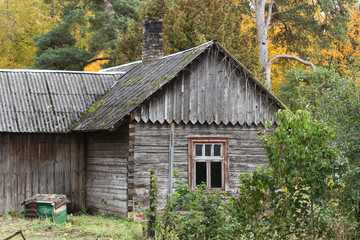 Old countryside farmside house abandoned near forest trees.