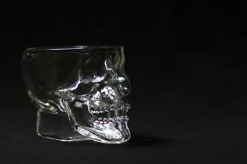 Transparent glass-skull on a black background close-up.