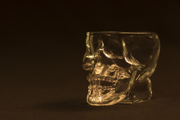 An unusual glass for a Halloween party in the form of a skull skeleton on a dark background. Empty, transparent, toned, close-up.