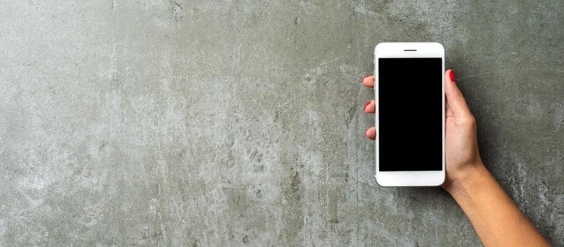 Female hand holding white mobile phone