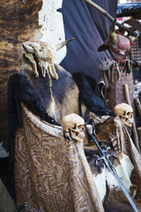 Throne of skins with skulls and Viking sword. Medieval chair with animal skins and horns