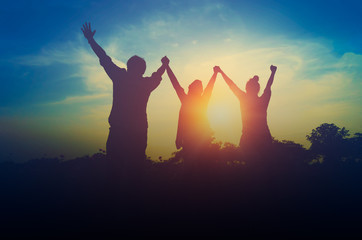 Silhouette of happy teamwork hold hands up as a business successful, business victory