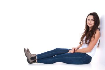 Junge Frau sitzt vor weißem Hintergrund