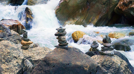 Сairns, a human-made piles, or stacks, of stones, on Modi Khola river in Himalaya mountains, Nepal. Nature background.