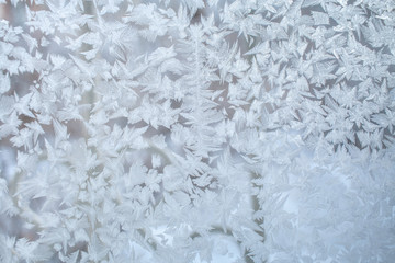 Frosty pattern on window glass with strips and fantastic snowflakes.